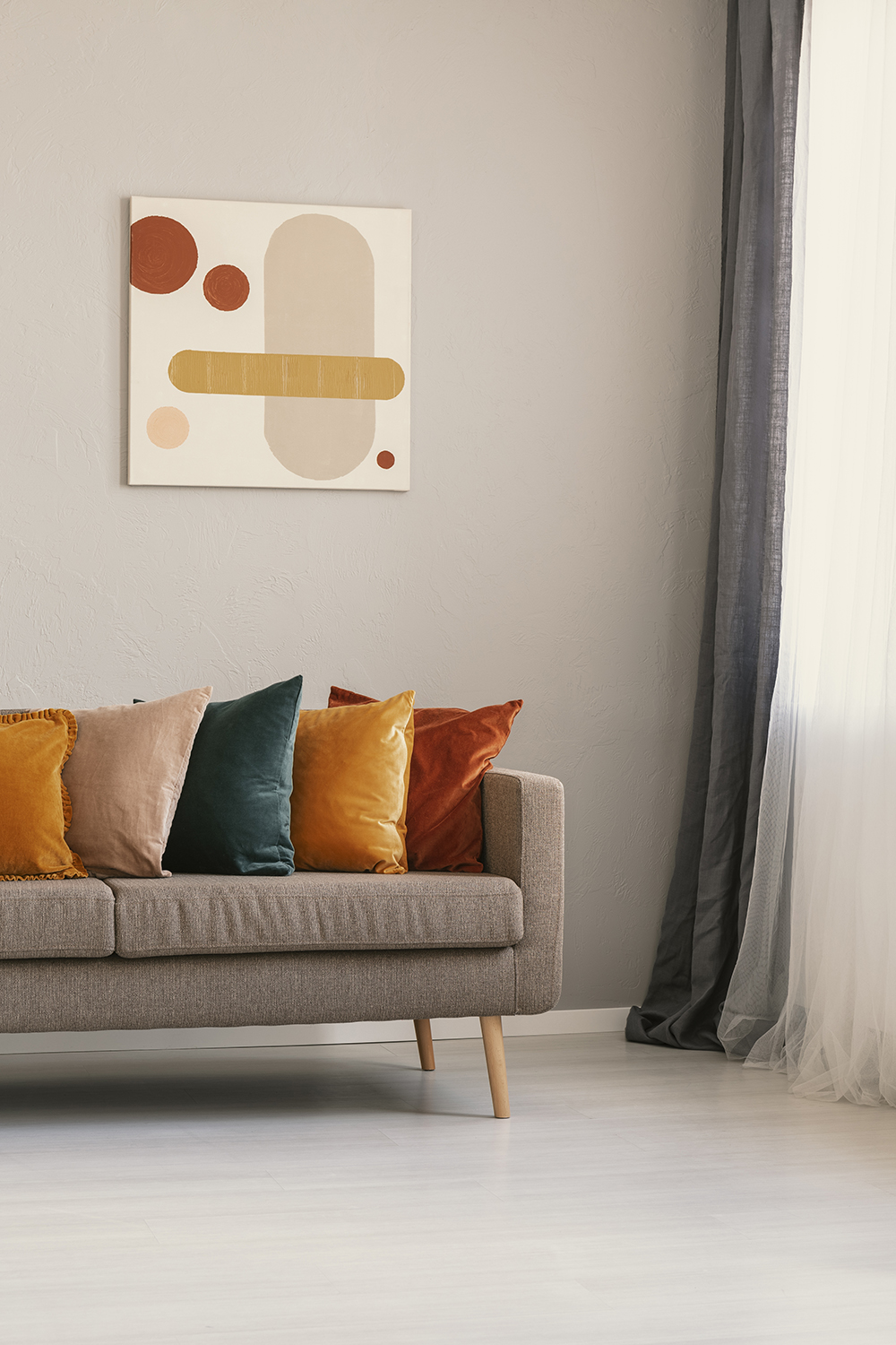 Abstract painting on beige wall above brown sofa with colorful pillows