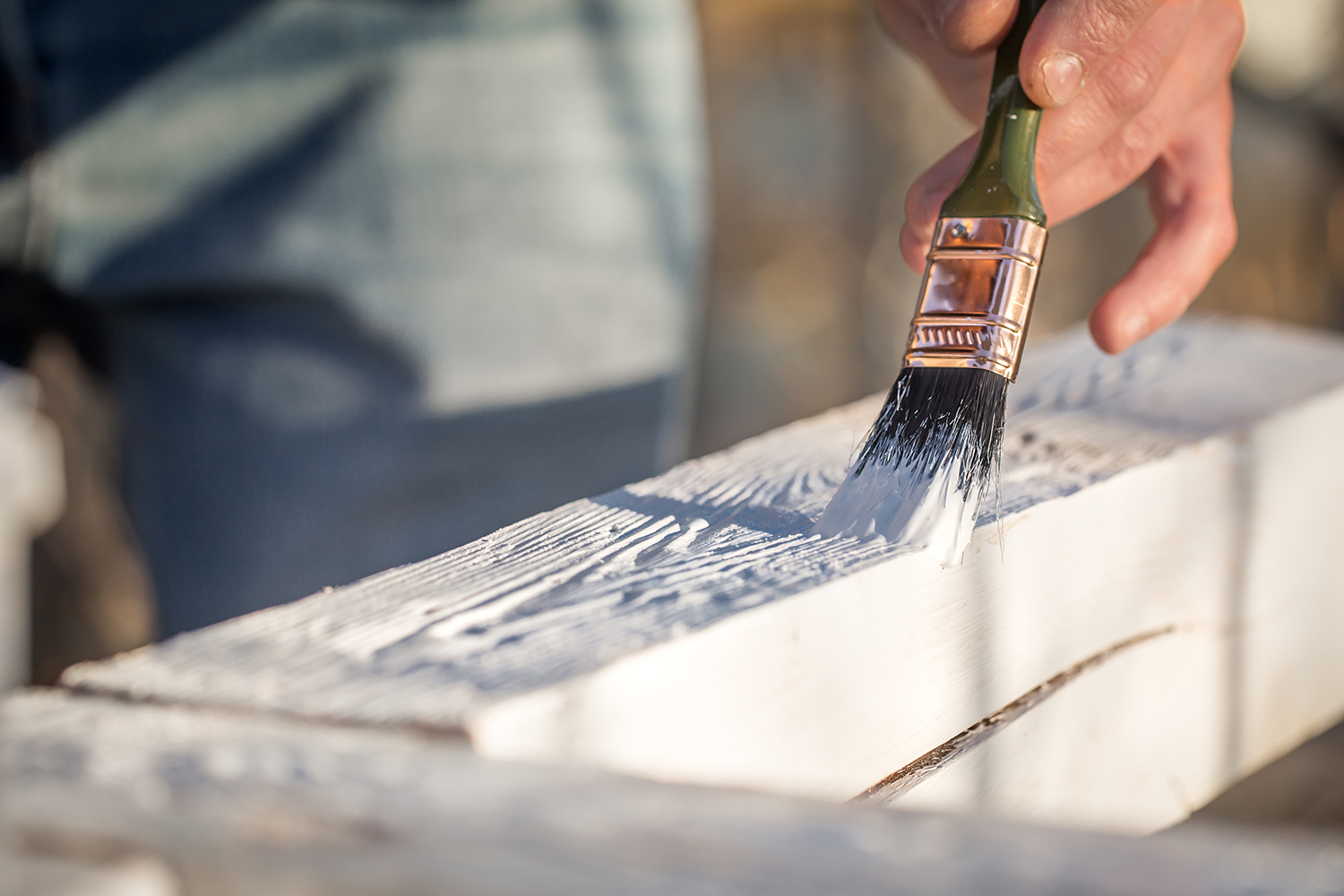 male hand paints with white paint on wood